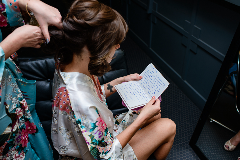 bride getting ready, reading letter from groom at The Belmont by wedding photographer in austin