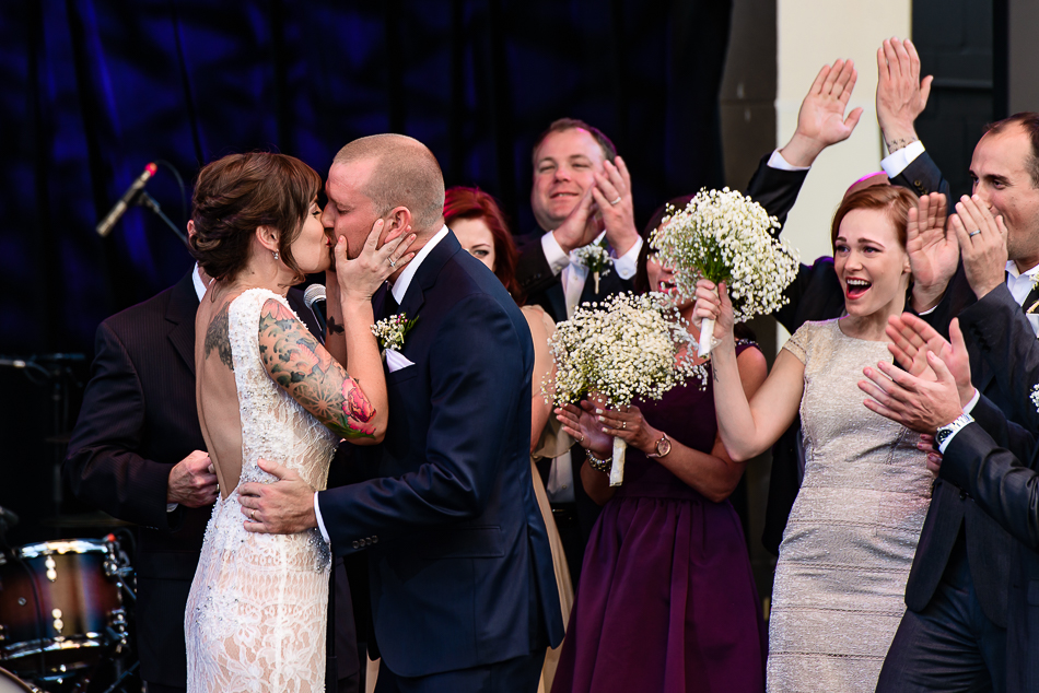 ceremony kiss, stylish couple with tattoos by austin wedding photographer on stage at The Belmont