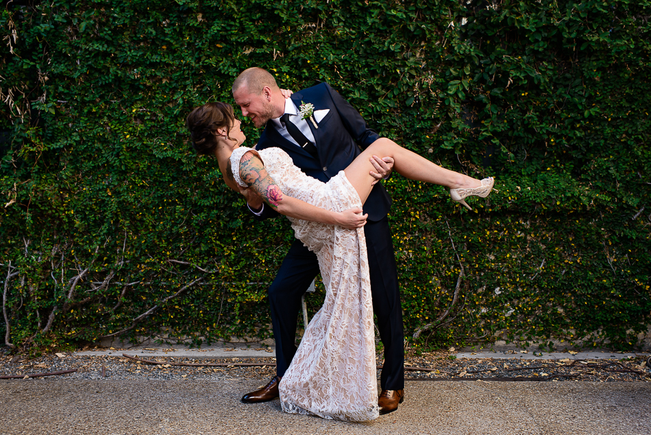 sexy portrait of groom dipping tattooed bride during reception by austin wedding photographer