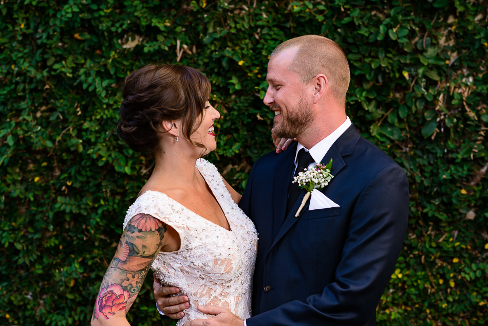 portrait of tattooed bride and groom in front of ivy wall by austin photographer