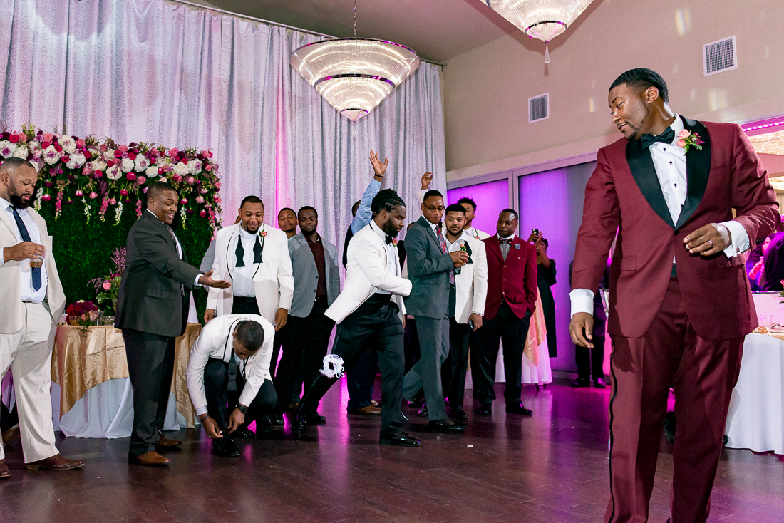 Black groom garter toss with purple uplighting by austin wedding photographers