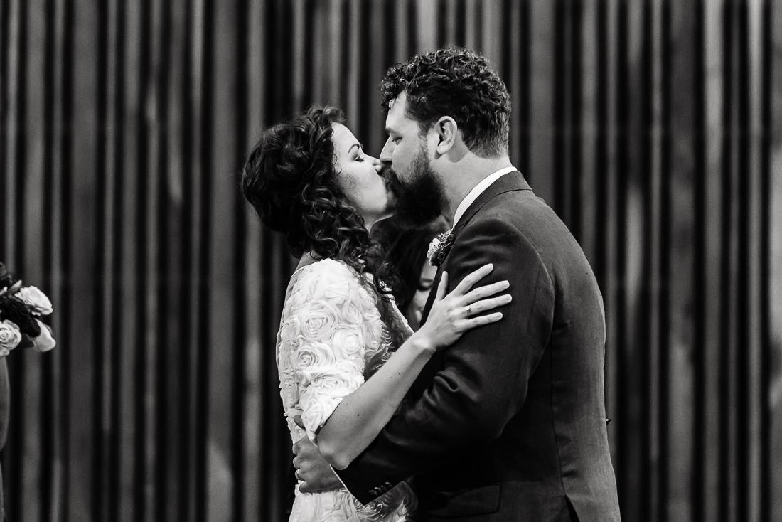 ceremony-Austin-Wedding-Photographers-kiss-ceremony-altar-black-white-groom-bride