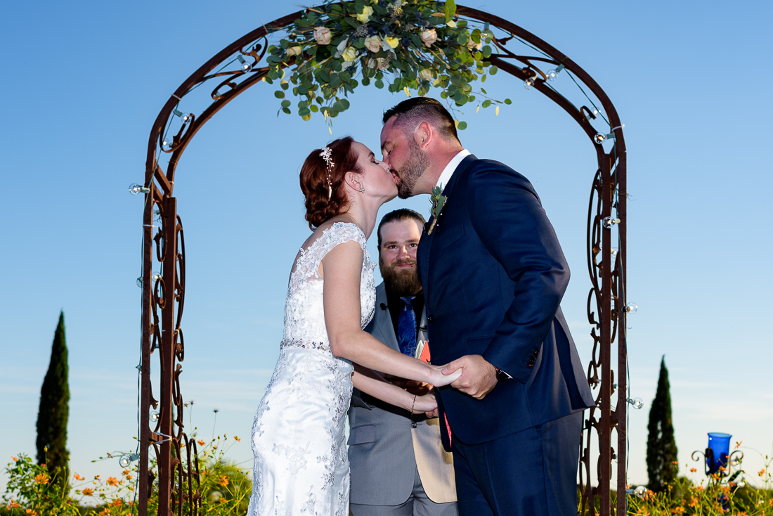 Trellis flowers ceremony outdoor kiss austin wedding photographers