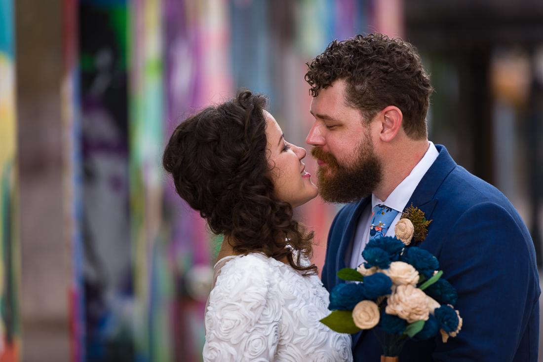 groom-bride-Austin-Wedding-Photographers-portraits-downtown-tx-mural-graffiti-colorful-kiss