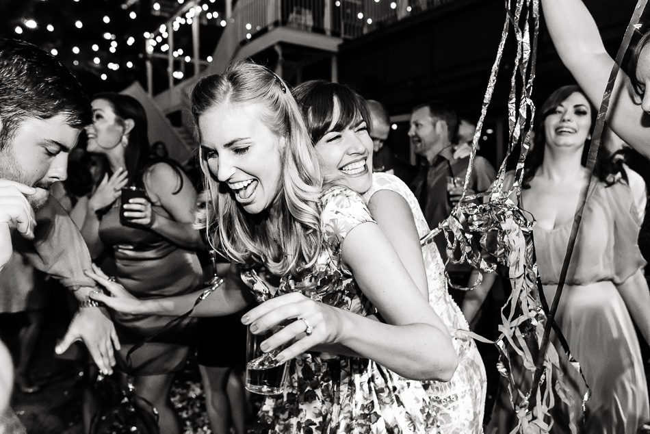 Bride having fun hugging a friend during outdoor wedding reception by austin wedding photographer