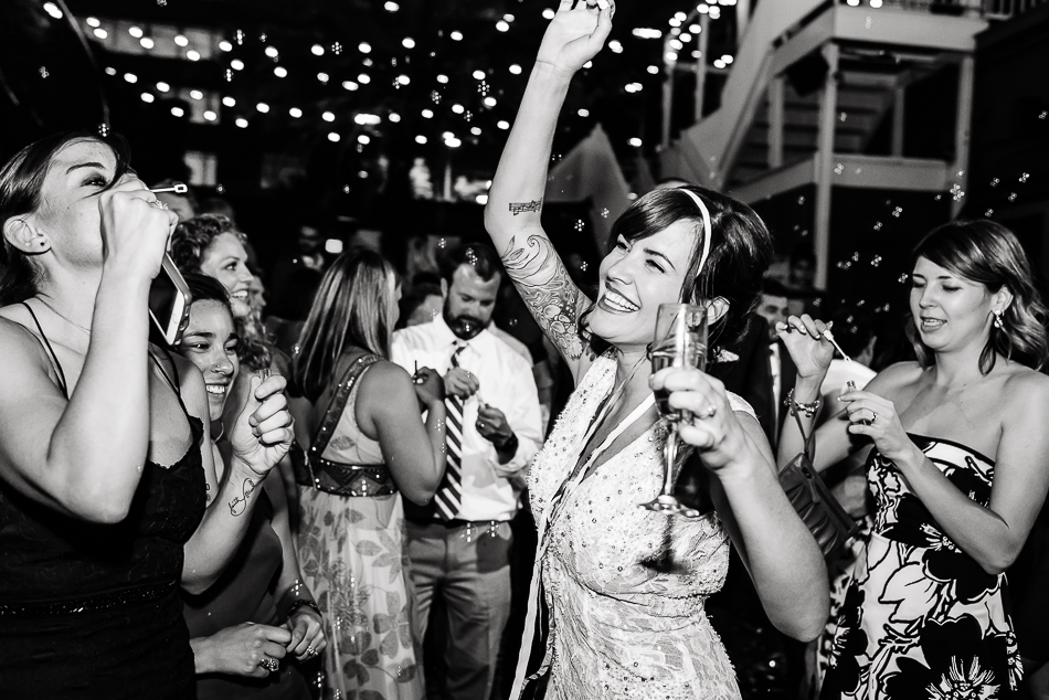Bride with tattoos dancing and drinking champagne while friends blow bubbles by austin wedding photographer